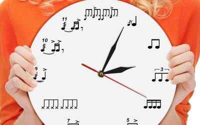 Image of a lady in an orange shirt holding a clock for drummers