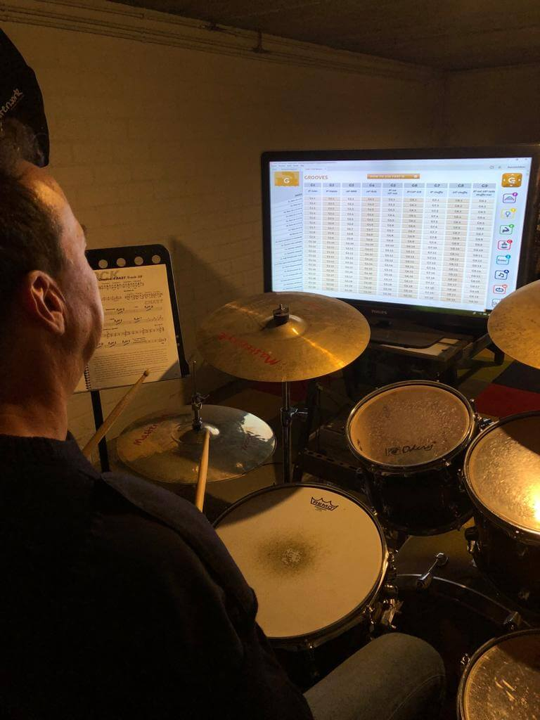 Drummer girl practicing the drums while studying out of the 3D Druming System by Skillz Drum Lessons